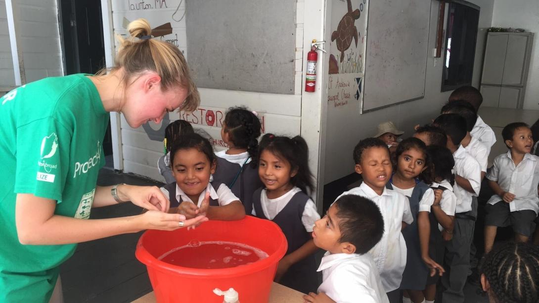 Public Health volunteers helps young girls wash glitter off their hands